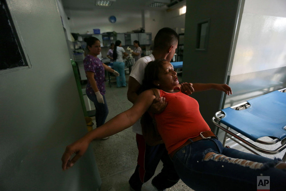 Joyce Brito is tended to by emergency room personnel after she was wounded in the chin during clashes with the Venezuelan Bolivarian National Guard in Urena, Venezuela, near the border with Colombia, Saturday, Feb. 23, 2019. (AP Photo/Fernando Llano)