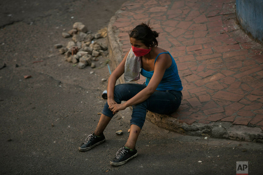 An opposition demonstrator rests after clashing with the Bolivarian National Guard in Urena, Venezuela, near the border with Colombia, Saturday, Feb. 23, 2019. (AP Photo/Rodrigo Abd)