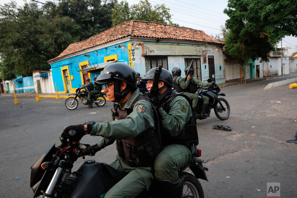 Venezuelan Bolivarian National Guards patrol on motorcycles clashes with protesters in Urena, Venezuela, near the border with Colombia, Saturday, Feb. 23, 2019. (AP Photo/Rodrigo Abd)
