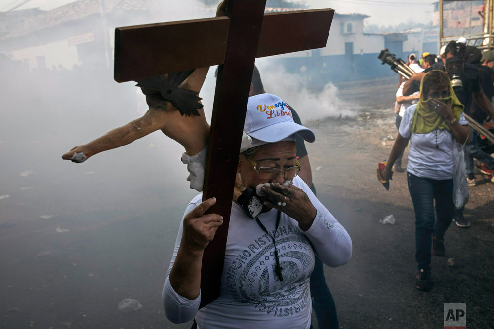 A woman carries a cross amid tear gas during clashes between the opposition and the Venezuelan Bolivarian National Guard in Urena, Venezuela, near the border with Colombia, Saturday, Feb. 23, 2019. (AP Photo/Rodrigo Abd)