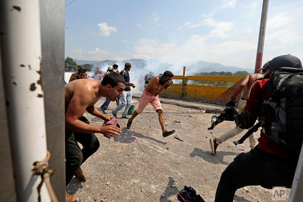 People run for cover from tear gas launched by Venezuela's National Guard as they try to clear the barricaded Simon Bolivar international bridge in Cucuta, Colombia, Saturday, Feb. 23, 2019. (AP Photo/Fernando Vergara)