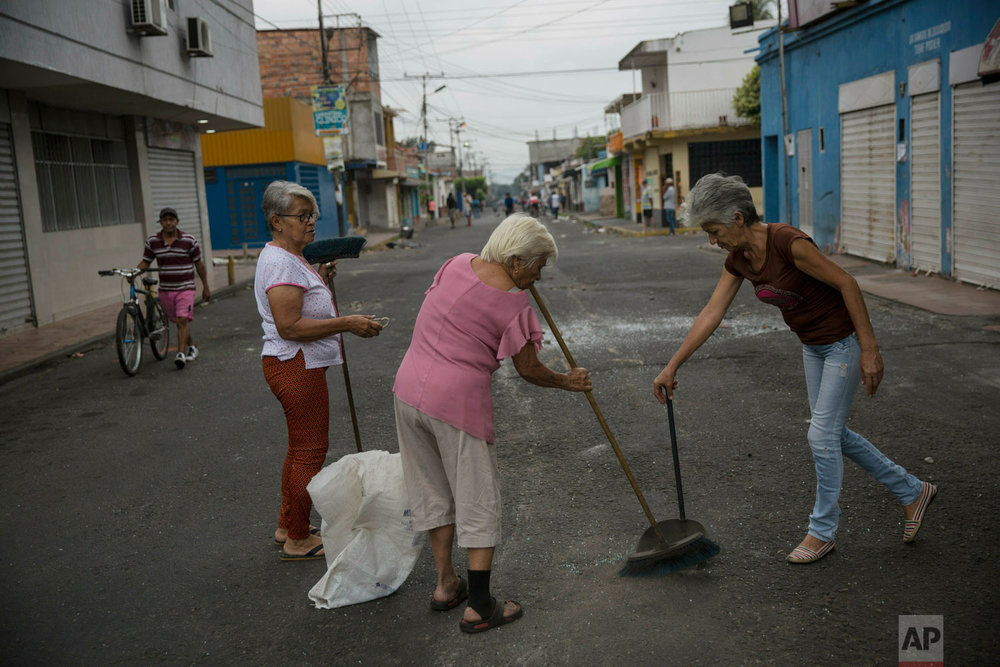 Neighbors clean the streets a day after clashes between anti-government protesters and the Venezuelan Bolivarian National Guard in Urena, Venezuela, near the border with Colombia, Sunday, Feb. 24, 2019. (AP Photo/Rodrigo Abd)