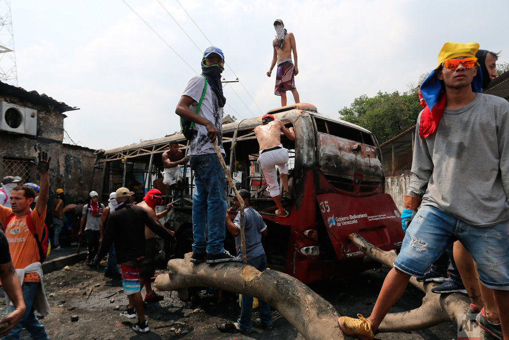 Demonstrators stand on a torched bus during clashes with the Venezuelan Bolivarian National Guard in Urena, Venezuela, near the border with Colombia, Saturday, Feb. 23, 2019. (AP Photo/Rodrigo Abd)
