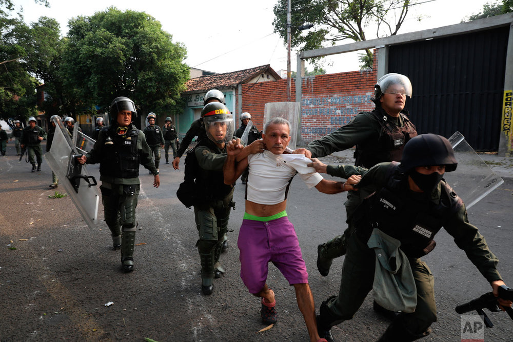A man is detained during clashes with the Venezuelan Bolivarian National Guard in Urena, Venezuela, near the border with Colombia, Saturday, Feb. 23, 2019. (AP Photo/Rodrigo Abd)