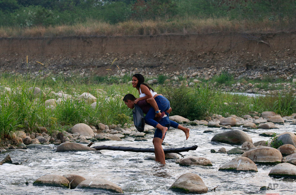 A young woman is carried across the Tachira River at the border between Venezuela and Colombia to attend the Venezuela Aid Live concert in Palotal, Venezuela, Friday, Feb. 22, 2019. (AP Photo/Fernando Llano)