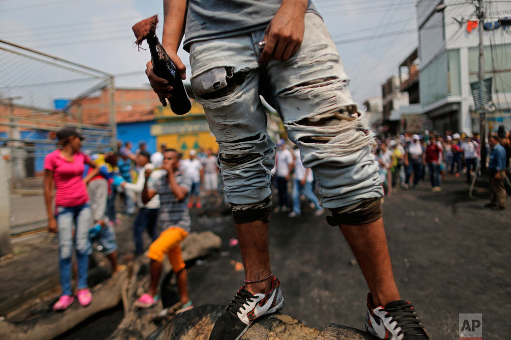 A demonstrator stands on a barricade with a gasoline bomb during clashes with the Venezuelan Bolivarian National Guard in Urena, Venezuela, near the border with Colombia, Saturday, Feb. 23, 2019. (AP Photo/Rodrigo Abd)