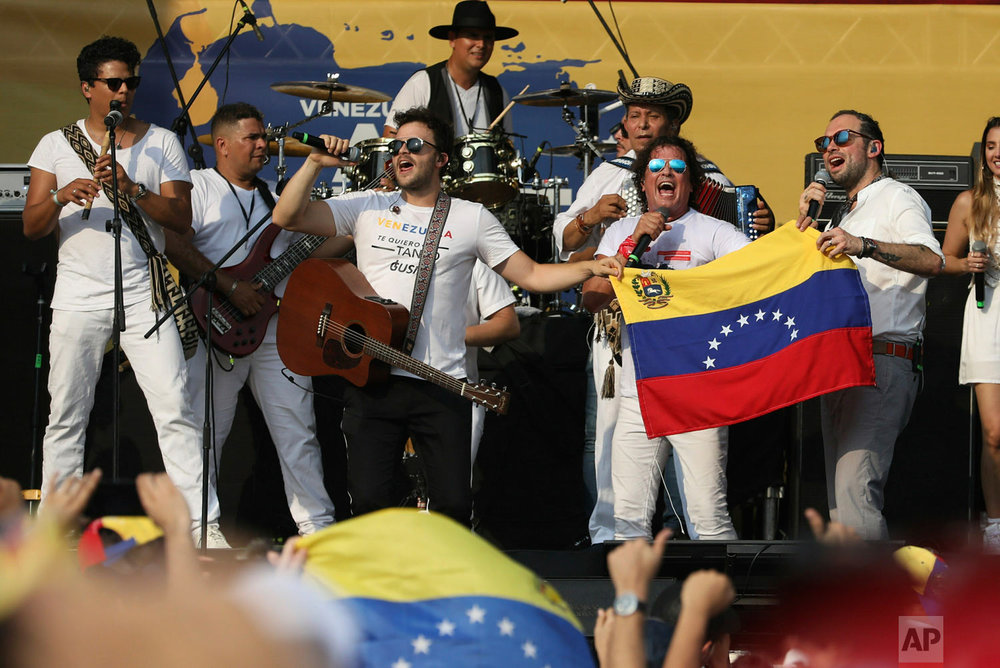 Gusi, left center, and Santiago Cruz, far right, hold a Venezuelan national flag as they perform with Carlos Vives at the Live Aid Venezuela concert at the Tienditas International Bridge on the outskirts of Cucuta, Colombia, Friday, Feb. 22, 2019, on the border with Venezuela. (AP Photo/Fernando Vergara)