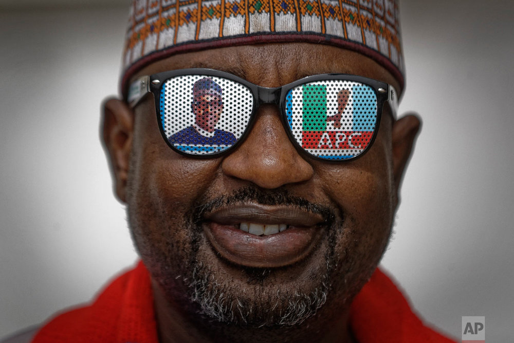 A supporter of incumbent President Muhammadu Buhari wears sunglasses with a photo of Buhari and the initials of his All Progressives Congress (APC) party, at a campaign rally in Abuja, Nigeria, Feb. 13, 2019. (AP Photo/Ben Curtis)