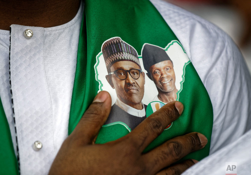 A supporter of incumbent President Muhammadu Buhari, wearing a sticker of Buhari and and Vice President Yemi Osinbajo, stands for the national anthem at a campaign rally in Abuja, Nigeria, Feb. 13, 2019. (AP Photo/Ben Curtis)