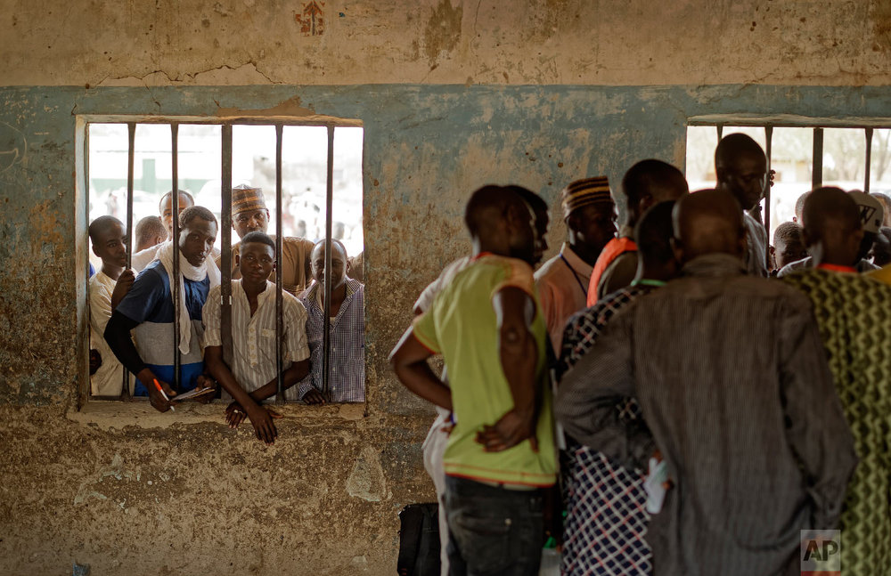People peer through a window as party agents huddle together to watch votes being counted inside a polling station in Kano, northern Nigeria, Feb. 23, 2019. (AP Photo/Ben Curtis)