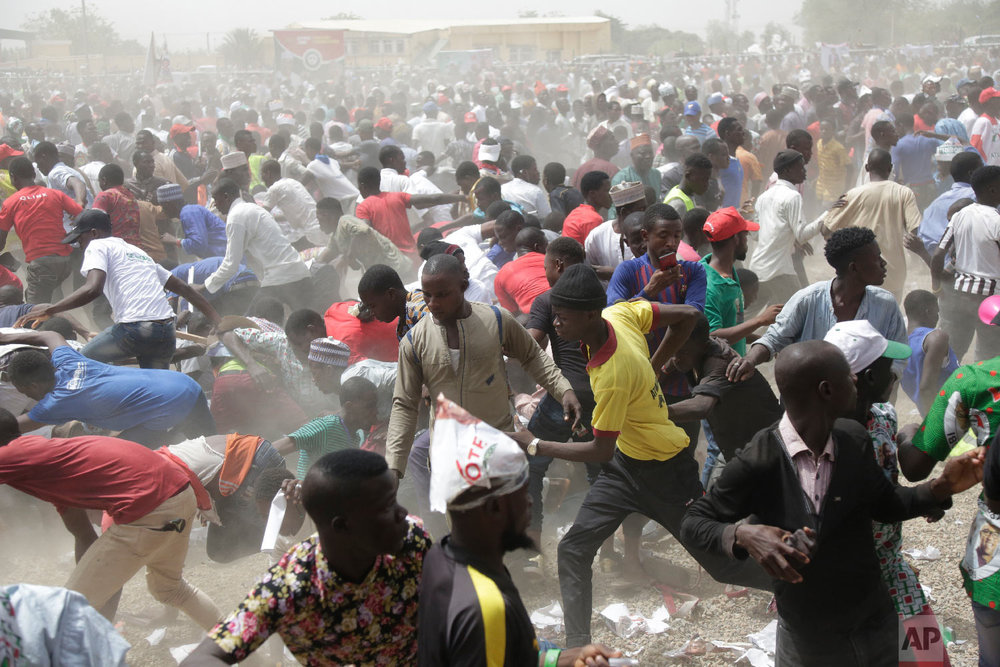Supporters of Nigerian presidential candidate Atiku Abubakar, of the People's Democratic Party run after being chased by local security during an election campaign rally at the Ribadu Square in Yola, Nigeria, Feb. 14, 2019. (AP Photo/Sunday Alamba)