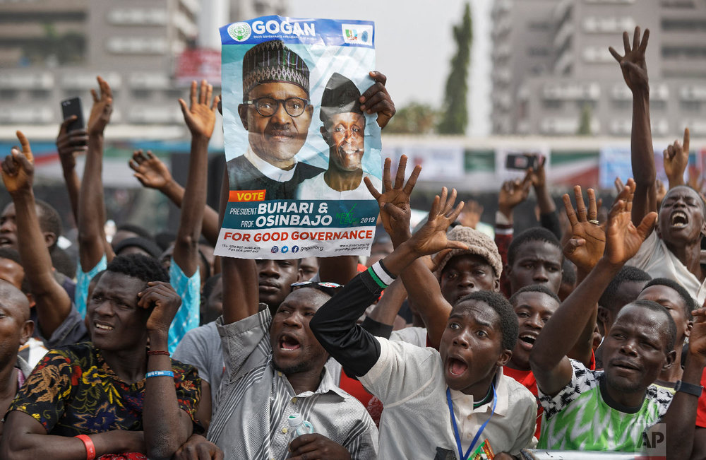 Supporters of incumbent President Muhammadu Buhari, holding a poster of Buhari and and Vice President Yemi Osinbajo, cheer as he arrives at a campaign rally in Abuja, Nigeria, Feb. 13, 2019. (AP Photo/Ben Curtis)