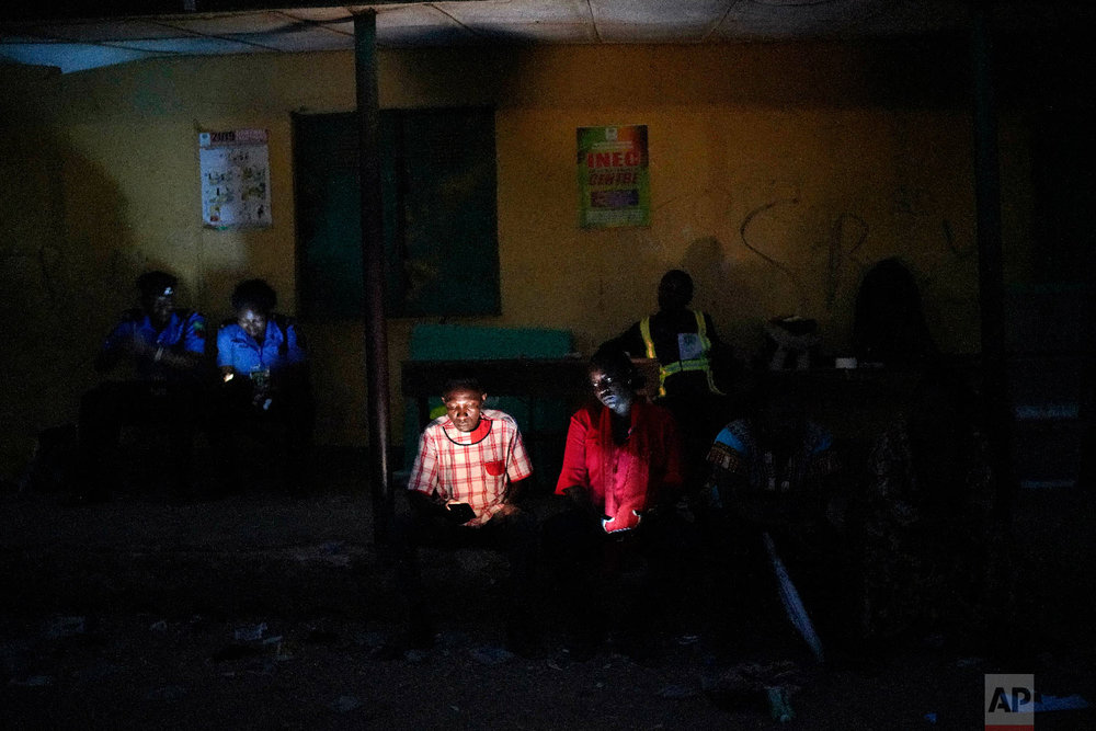 Nigerian election volunteers and police wait for votes to finish being counted in Kaduna, Nigeria, Feb. 23, 2019. (AP Photo/Jerome Delay)
