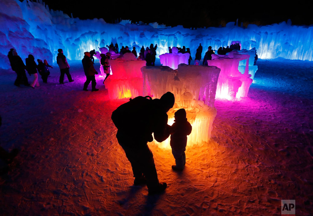 Bruce McCafferty and his son, Dougie, pause while explore the ice formations growing at Ice Castles, in North Woodstock, N.H., on Jan. 26, 2019. (AP Photo/Robert F. Bukaty)