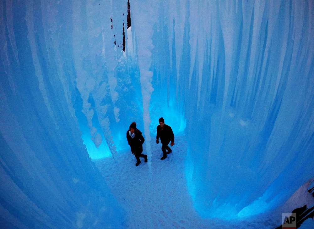 Visitors walk through a cavern at Ice Castles on Jan. 26, 2019, in North Woodstock, N.H. (AP Photo/Robert F. Bukaty)