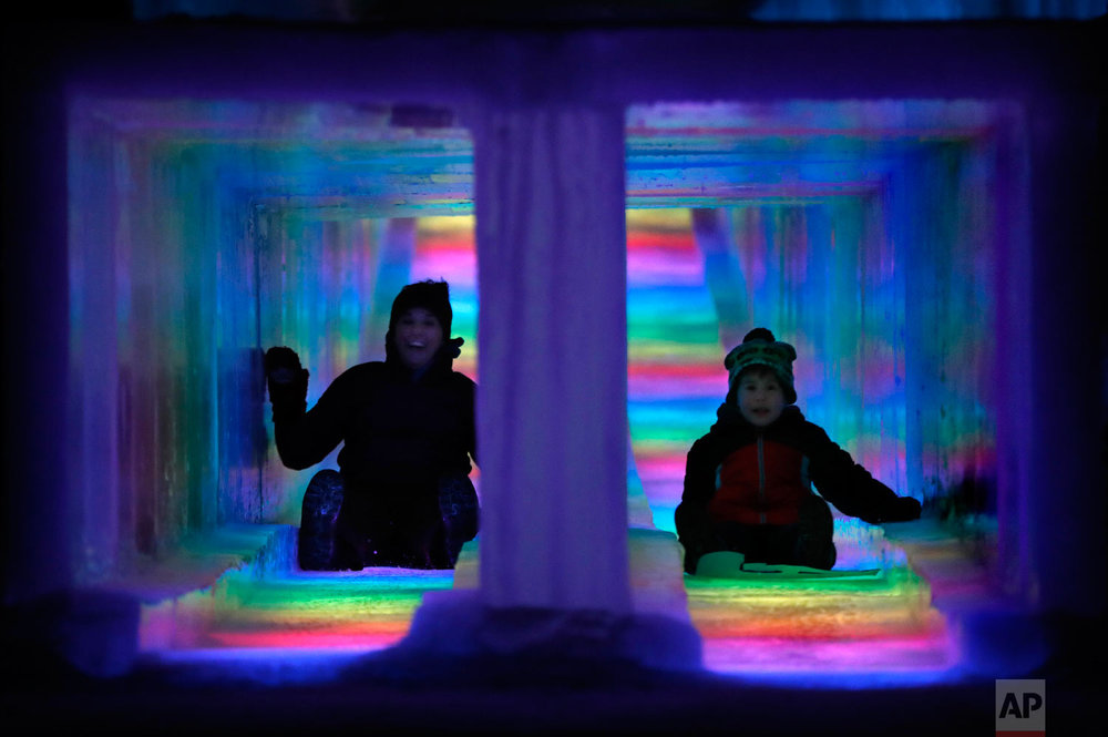 Visitors race down the side-by-side tunnels of a 97-foot ice slide at Ice Castles in North Woodstock, N.H., on Jan. 25, 2019. (AP Photo/Robert F. Bukaty)