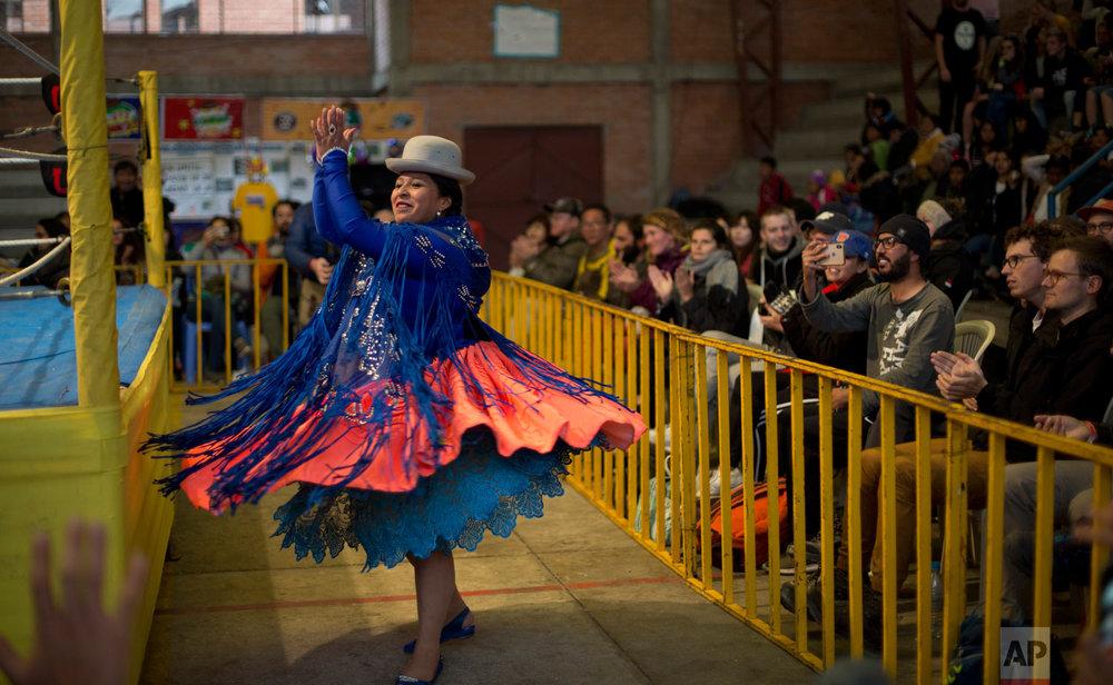 Veteran cholita wrestler Leydi Huanca, 29, whose real name is Reyna Torrez, dances as she enters the ring area to compete in El Alto, Bolivia, Sunday, Feb. 10, 2019. (AP Photo/Juan Karita)