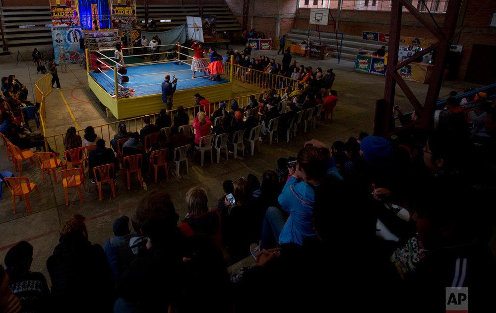 Veteran cholita wrestler Reyna Torrez stands in the corner of the ring as she competes with teen fighter Dona Chevas in El Alto, Bolivia, Sunday, Feb. 10, 2019. (AP Photo/Juan Karita)