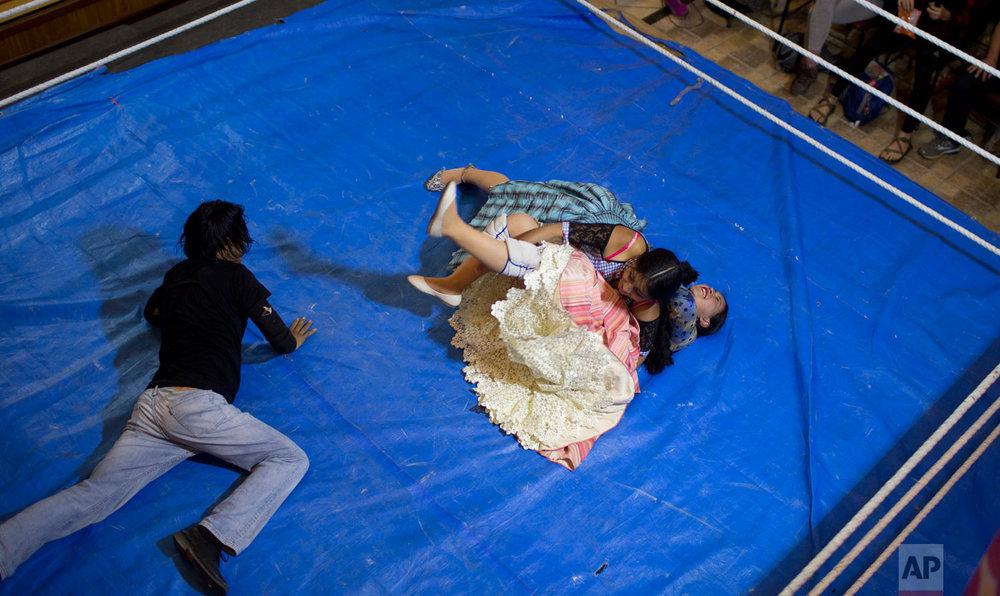 Cholita wrestler Natalia Pepita, 19, is held down by fellow fighter in training, Wara, 22, in the ring in El Alto, Bolivia, Thursday, Feb. 7, 2019. (AP Photo/Juan Karita)