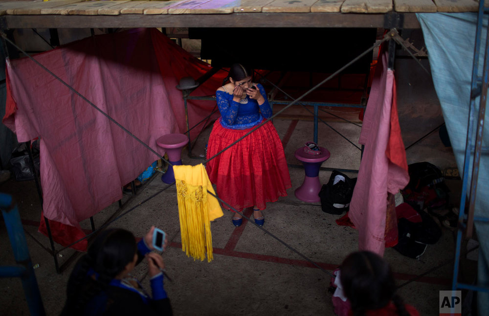Young cholita wrestler Wara puts her makeup on before competing in the ring in El Alto, Bolivia, Sunday, Feb. 24, 2019. (AP Photo/Juan Karita)