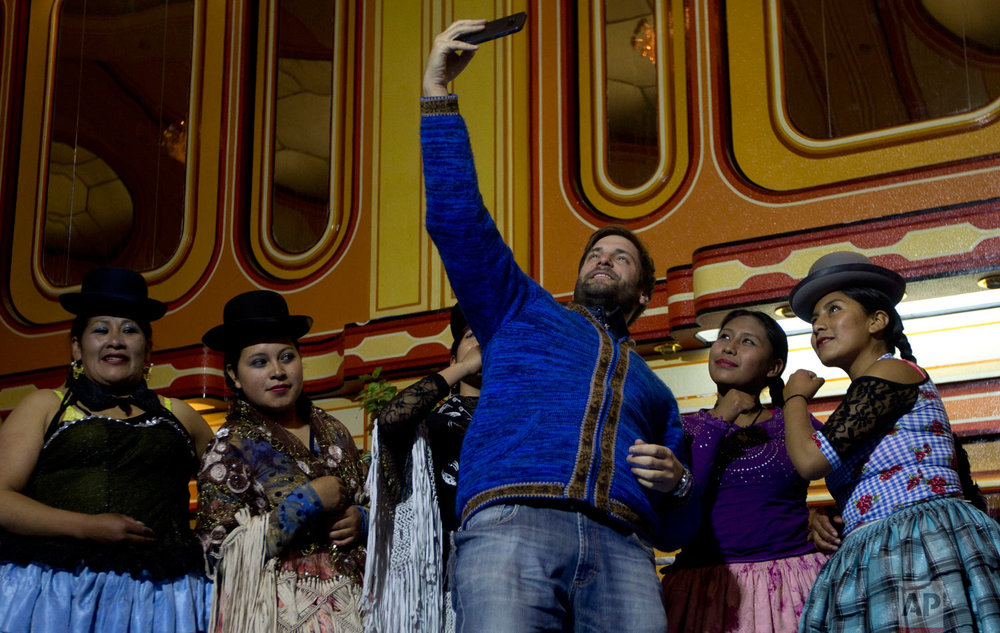 A tourist takes a selfie with cholita wrestlers after they competed in the ring in El Alto, Bolivia, Thursday, Feb. 7, 2019. (AP Photo/Juan Karita)