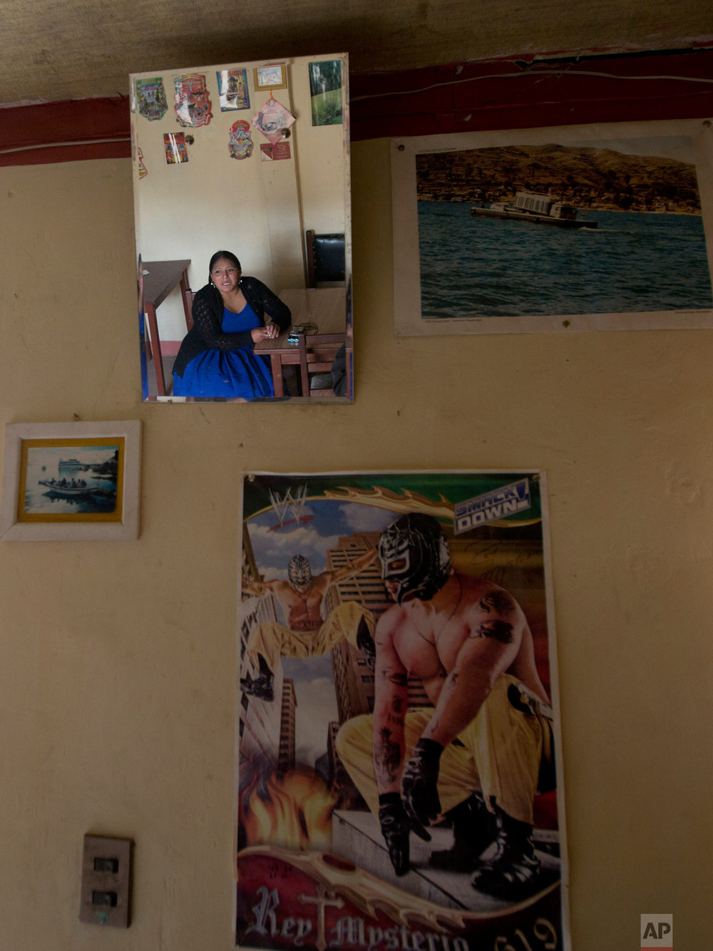Reyna Torrez is reflected in a mirror next to a poster of Mexican professional wrestler Rey Mysterio during an interview at her home in El Alto, Bolivia, Monday, Feb. 18, 2019. (AP Photo/Juan Karita)