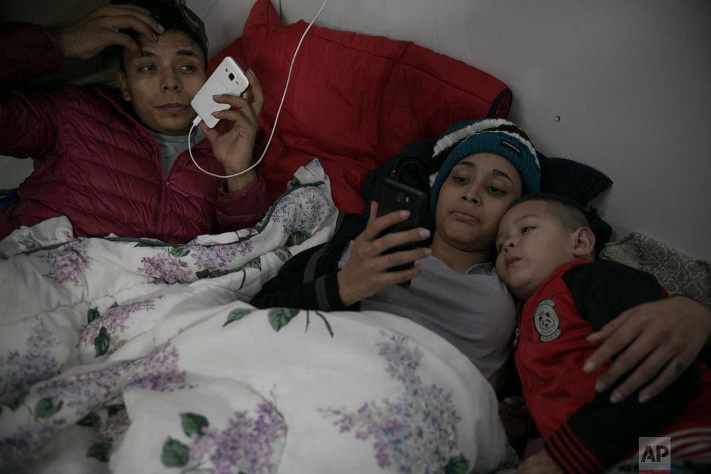 Teen Honduran migrants Josue Mejia Lucero, his girlfriend Milagro de Jesus Henriquez Ayala, 15, and Josue's 3-year-old nephew Jefferson, look at cell phones as they lie in bed at the Agape World Mission shelter in Tijuana, Mexico, Feb. 8, 2019. (AP Photo/Emilio Espejel)