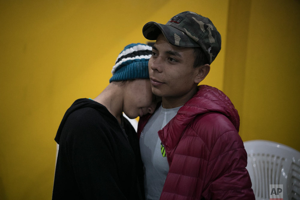 Central American teen migrants, Milagro de Jesus Henriquez Ayala, 15, and Josue Mejia Lucero, 17, embrace at the end of a Christian religious service in the Agape World Mission shelter in Tijuana, Mexico, Feb. 8, 2019. (AP Photo/Emilio Espejel)