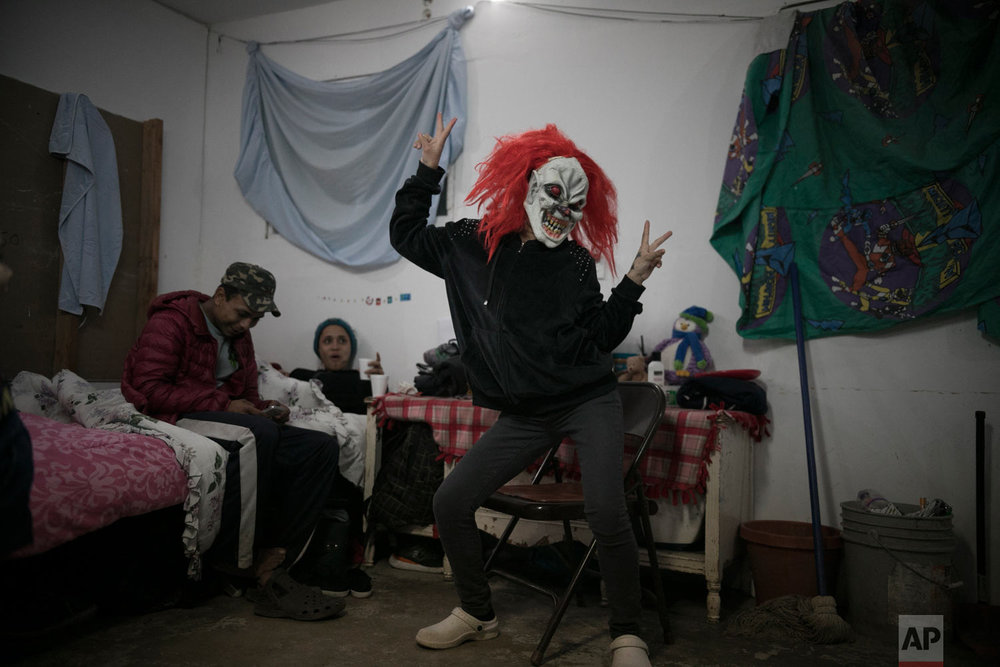 Central American teen migrants, 17-year-old Josue Mejia Lucero, left, and 15-year-old Milagro, relax on their bed as Milagro's sister Xiomara, 13, jokes around in a clown mask, at the Agape World Mission shelter where they are staying in Tijuana, Mexico, Feb. 8, 2019. (AP Photo/Emilio Espejel)