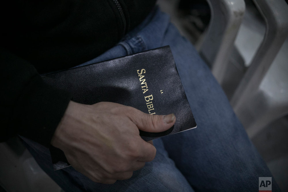 A migrant from Honduras holds a bible during a Christian religious service at the Agape World Mission shelter in Tijuana, Mexico, Feb. 8, 2019. (AP Photo/Emilio Espejel)