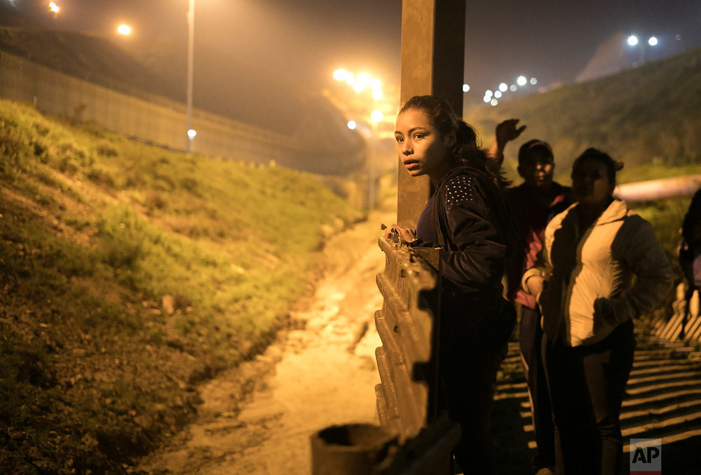 El Salvador migrant Xiomara Henriquez Ayala, 13, peers over the U.S. border fence from Tijuana, Mexico, Feb. 8, 2019, as Honduran migrant Josue Mejia Lucero, 17, and his sister Lucero, 25, look on while looking for a way to help Lucero and her son cross undetected. (AP Photo/Emilio Espejel)