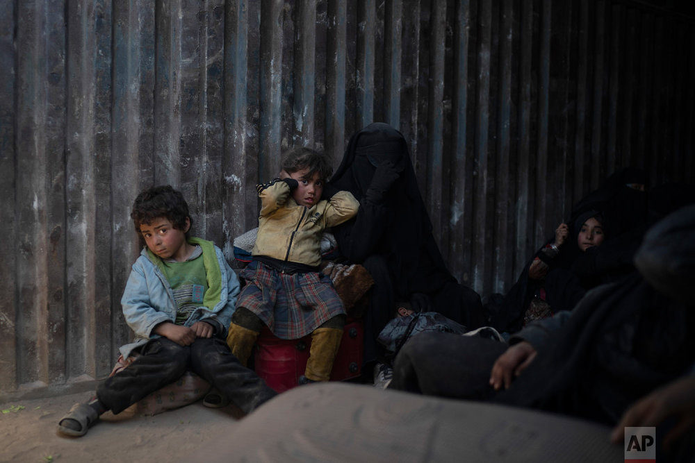 Women and children ride in the back of a truck that is part of a convoy evacuating hundreds out of the last territory held by Islamic State militants in Baghouz, eastern Syria, Feb. 20, 2019. (AP Photo/Felipe Dana)