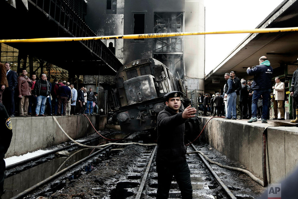 Policemen stand guard in front of a damaged train inside Ramsis train station in Cairo, Egypt, Feb. 27, 2019. (AP Photo/Nariman El-Mofty)