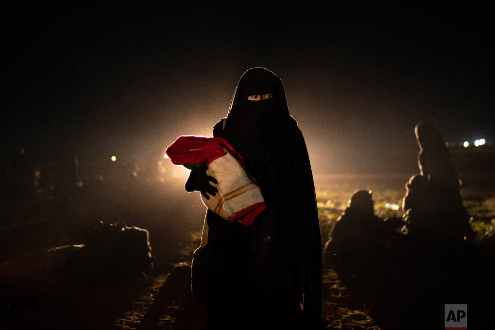 A woman who was evacuated out of the last territory held by Islamic State militants holds her baby after being screened by U.S.-backed Syrian Democratic Forces (SDF) in the desert outside Baghouz, Syria, Feb. 25, 2019. (AP Photo/Felipe Dana)
