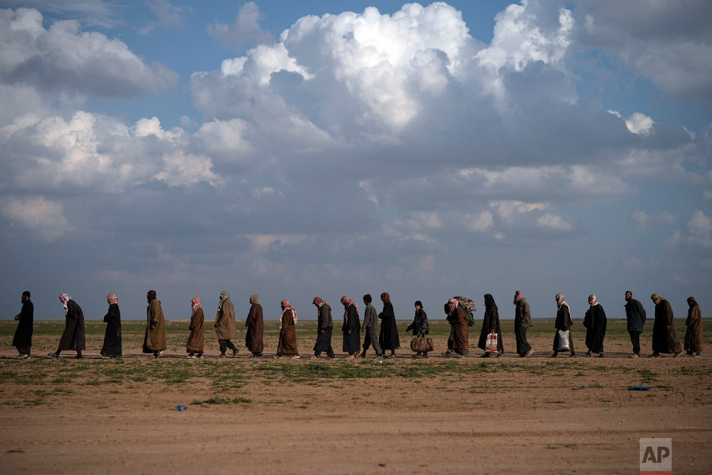 Men walk to be screened after being evacuated out of the last territory held by Islamic State militants, near Baghouz, eastern Syria, Feb. 22, 2019. (AP Photo/Felipe Dana)