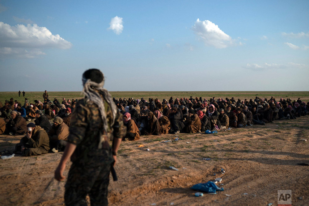 U.S.-backed Syrian Democratic Forces (SDF) fighters stand guard next to men waiting to be screened after being evacuated out of the last territory held by Islamic State militants, near Baghouz, eastern Syria, Feb. 22, 2019. (AP Photo/Felipe Dana)