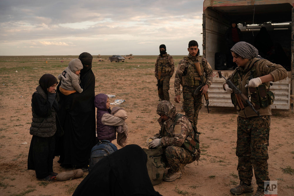Women and children are screened by U.S.-backed Syrian Democratic Forces (SDF) after being evacuated out of the last territory held by Islamic State militants, in the desert outside Baghouz, Syria, Feb. 27, 2019. (AP Photo/Felipe Dana)