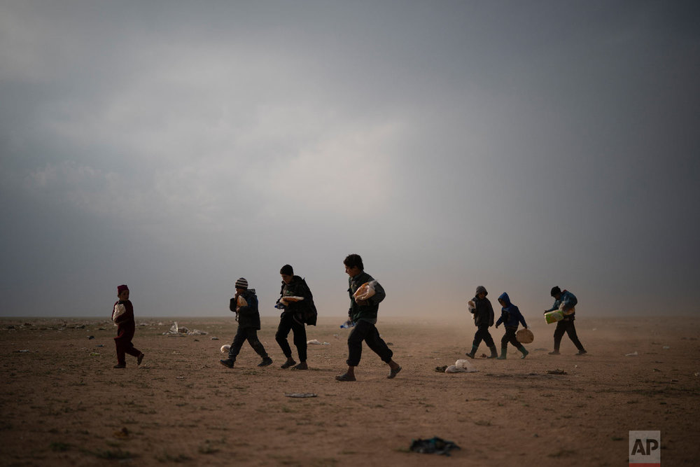 Children evacuated out of the last territory held by Islamic State militants walk at a screening center after collecting food, outside Baghouz, Syria, Feb. 26, 2019. Evacuations have continued amid a standoff between the militants and the U.S.-backed Syrian Democratic Forces (SDF). (AP Photo/Felipe Dana)