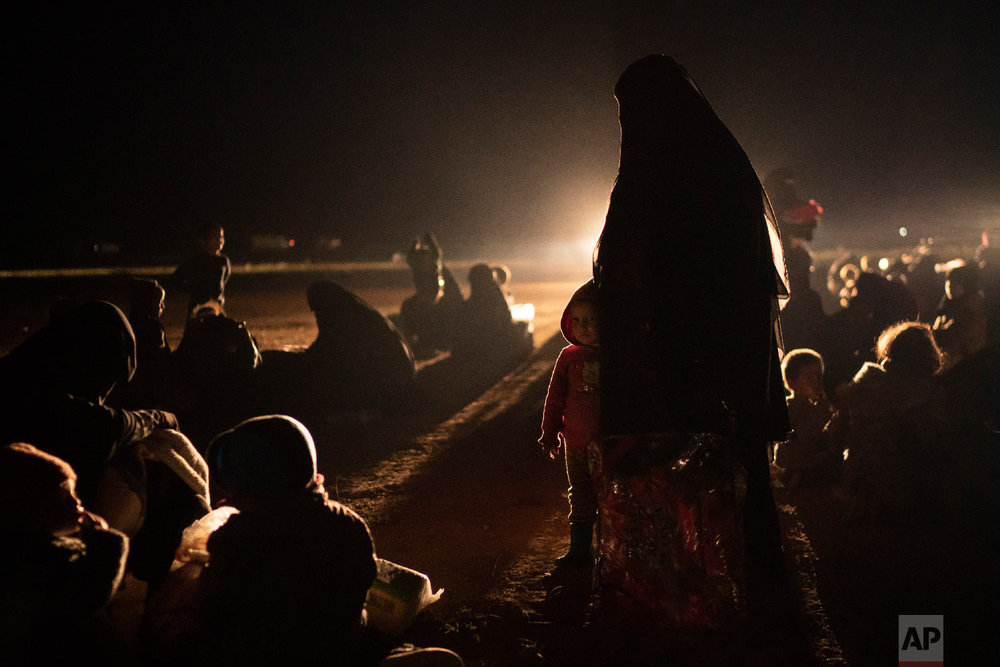 Women and children evacuated out of the last territory held by Islamic State militants wait after being screened by U.S.-backed Syrian Democratic Forces (SDF) in the desert outside Baghouz, Syria, Feb. 25, 2019. (AP Photo/Felipe Dana)