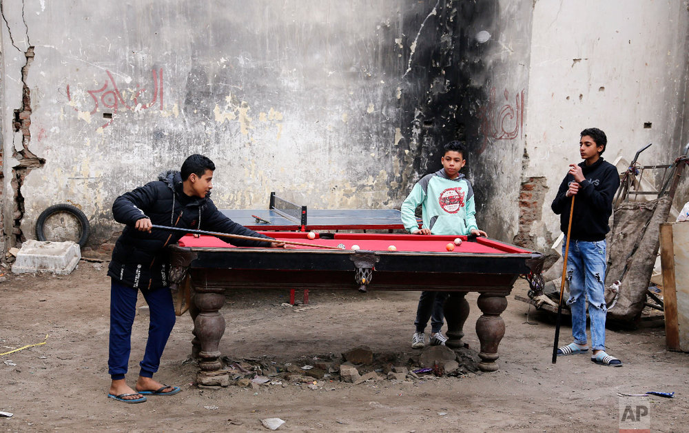 Boys play billiards as they hire a table for 4 EGP, (nearly $0.25), at Darb Shughlan popular district in Cairo, Egypt, Feb. 15, 2019. (AP Photo/Amr Nabil)