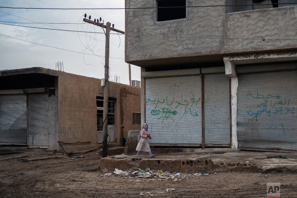 A girl walks in an area recently retaken by U.S.-backed Syrian Democratic Forces (SDF) from Islamic State militants in Hajin, Syria, Feb. 16, 2019. (AP Photo/Felipe Dana)