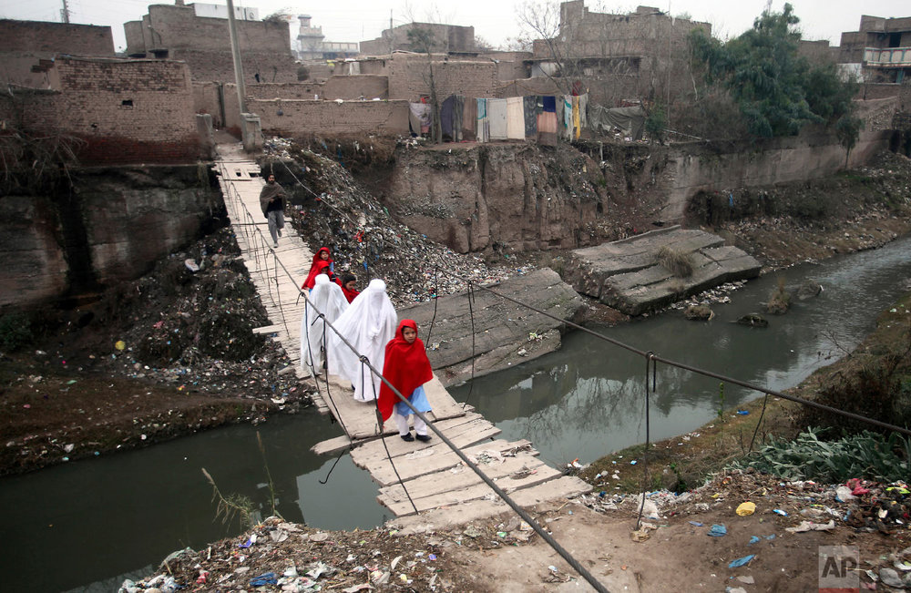 Villagers cross a makeshift bridge in a suburb of Peshawar, Pakistan, Feb. 4, 2019. The previous bridge was washed away in a flood. (AP Photo/Mohammad Sajjad)