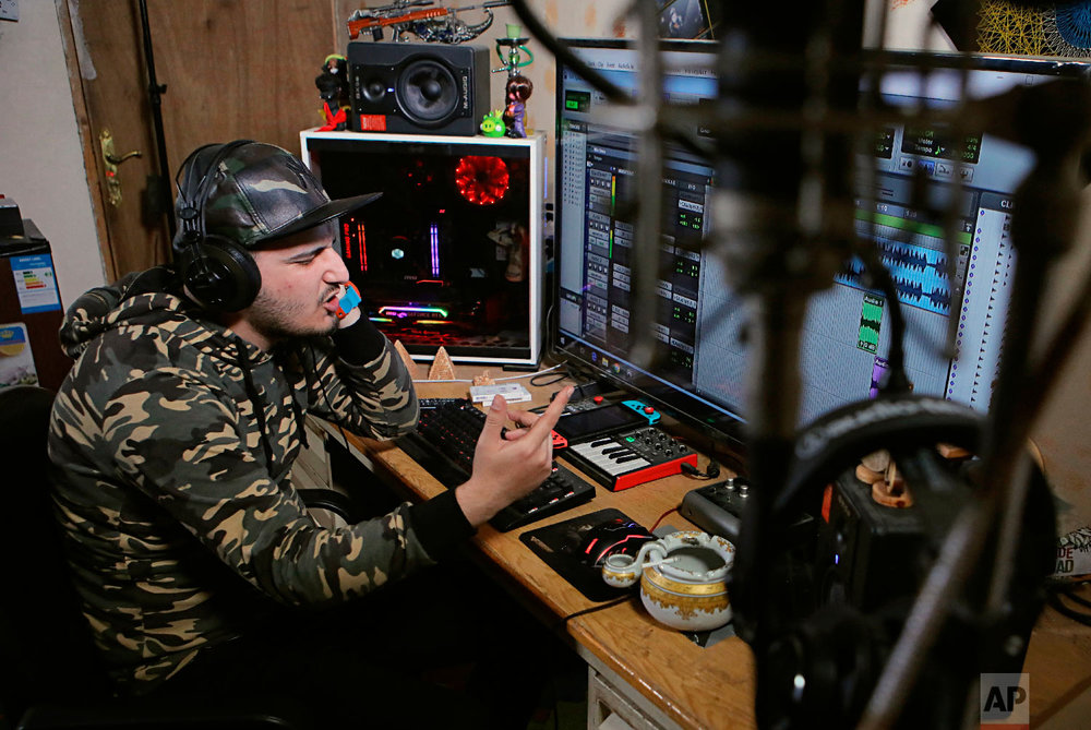 Rapper Ahmed Chayeb, goes by the name Mr. Guti, recording his soundtrack with his own computer at home in Basra, Iraq on Feb. 12, 2019. An Iraqi rapper raps about anger and disillusionment in his hometown, Basra, which saw riots last summer over failing services and soaring unemployment. (AP Photo/Nabil al-Jurani)