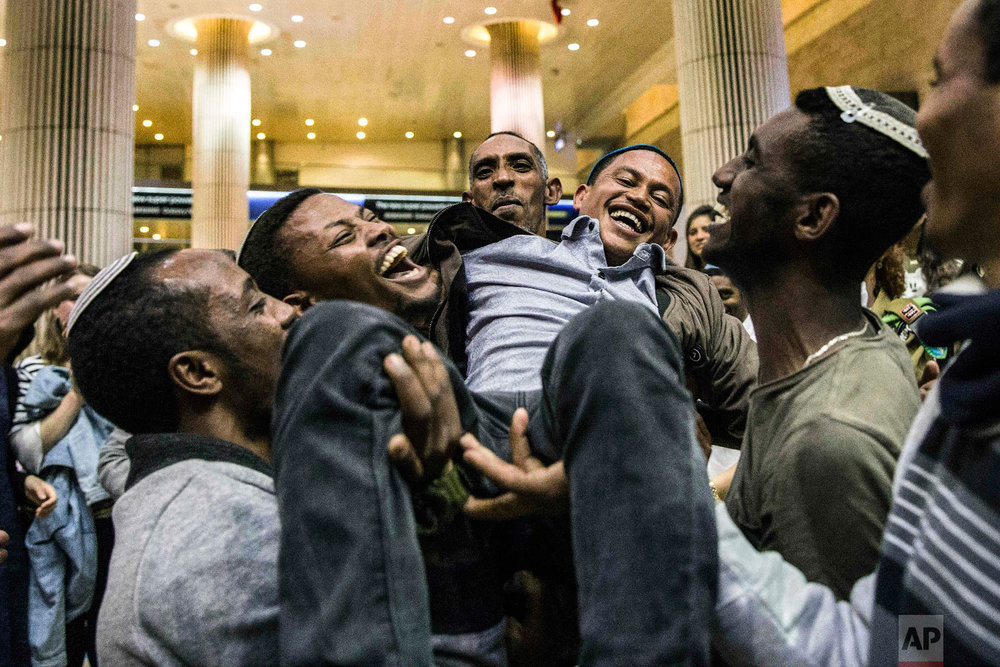 An Ethiopian Jew reunites with his family at the Ben Gurion Airport near Tel Aviv, Israel, early, Feb. 5, 2019. Nearly 100 Ethiopian Jews landed in Israel in the first wave of new immigration since the government said last year that it would let some of the 8,000 remaining community members join relatives in Israel. (AP Photo/Tsafrir Abayov)