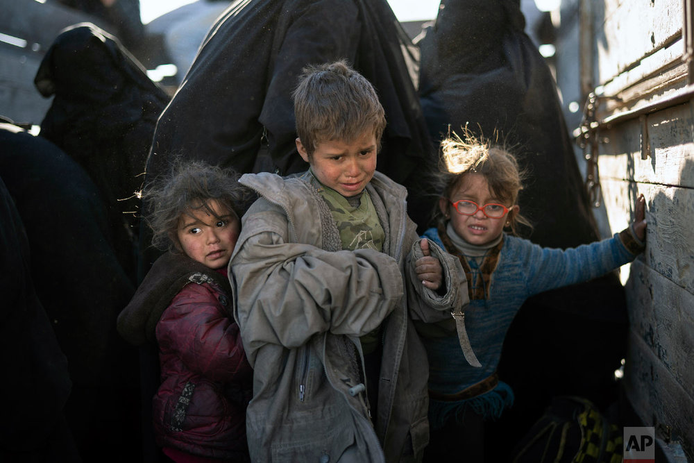 Women and children exit the back of a truck as they arrive at a U.S.-backed Syrian Democratic Forces (SDF) screening area after being evacuated out of the last territory held by Islamic State militants, in the desert outside Baghouz, Syria, Friday, March 1, 2019. (AP Photo/Felipe Dana)