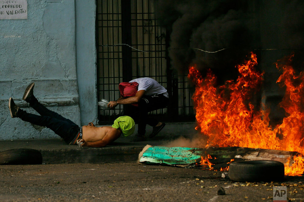 A demonstrator, left, falls after getting caught in a strand of barbed wire during clashes with the Bolivarian National Guard in Urena, Venezuela, near the border with Colombia, Saturday, Feb. 23, 2019. (AP Photo/Fernando Llano)