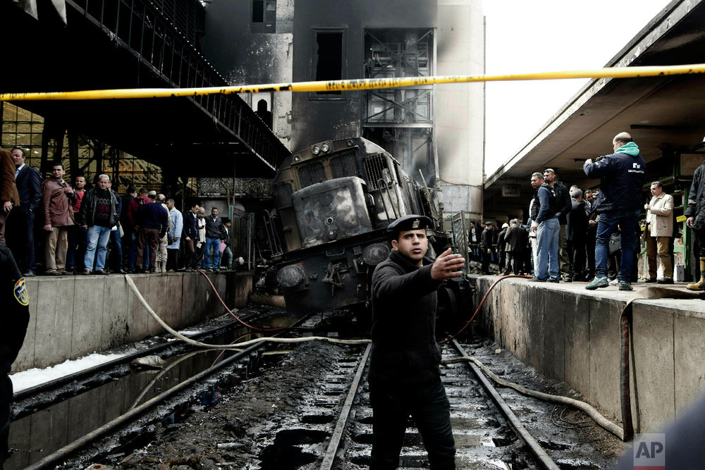 Policemen stand guard in front of a damaged train inside Ramsis train station in Cairo, Egypt, Wednesday, Feb. 27, 2019. (AP Photo/Nariman El-Mofty)
