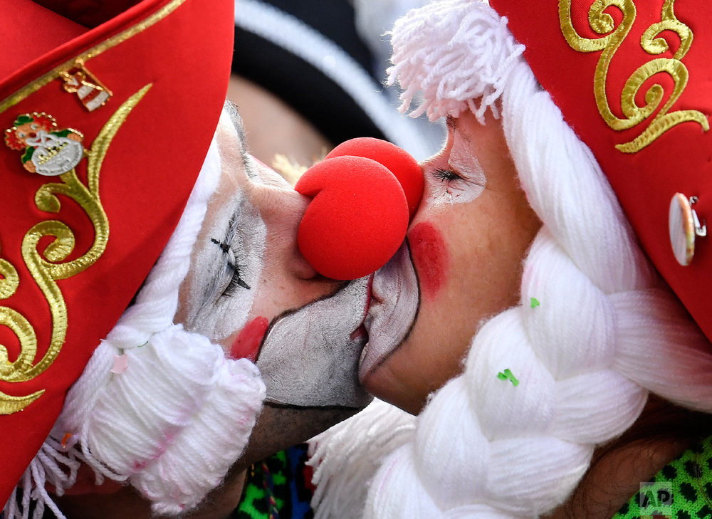Two revelers kiss for photographers in Cologne's city center when thousands of revelers dressed in carnival costumes celebrate the start of the street carnival in Cologne, Germany, Thursday, Feb. 28, 2019. (AP Photo/Martin Meissner)