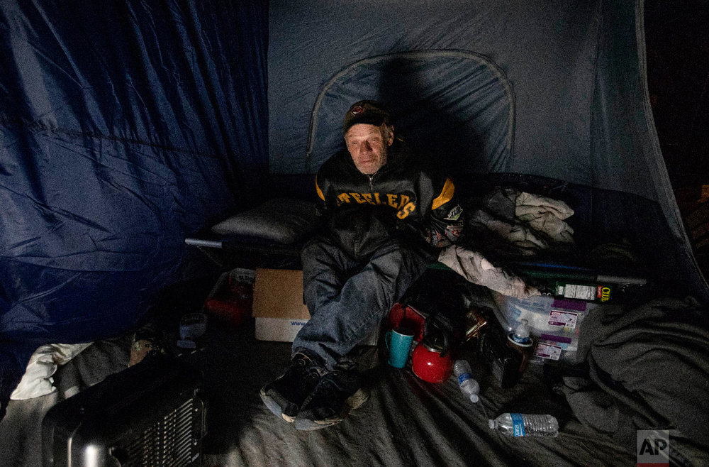 James Huebner sits in his tent in the backyard of a home where he's living with his son and brother after becoming homeless from Hurricane Michael in Youngstown, Fla, Wednesday, Jan. 23, 2019. (AP Photo/David Goldman)