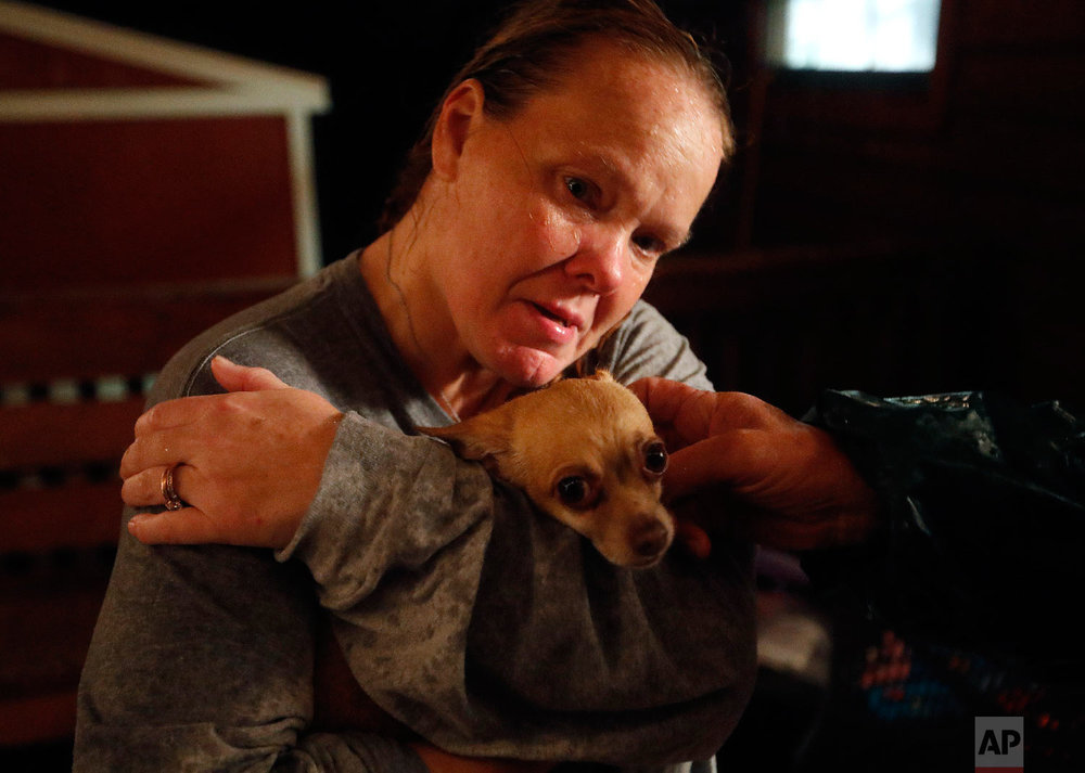 Lori Hogan, hugs her dog, Boo Boo, after losing him during a rain storm which brought on a panic attack for Hogan who is currently living in a tent in a backyard months after Hurricane Michael hit in Youngstown, Fla, Wednesday, Jan. 23, 2019. (AP Photo/David Goldman)